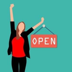 Confident business woman beside open sign - ideal customer